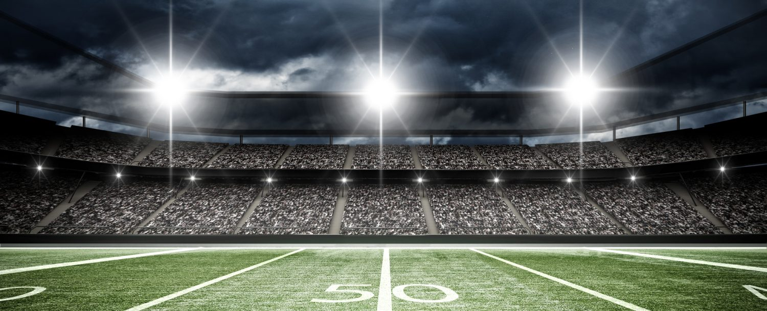 football field with dark sky, clouds, and lights