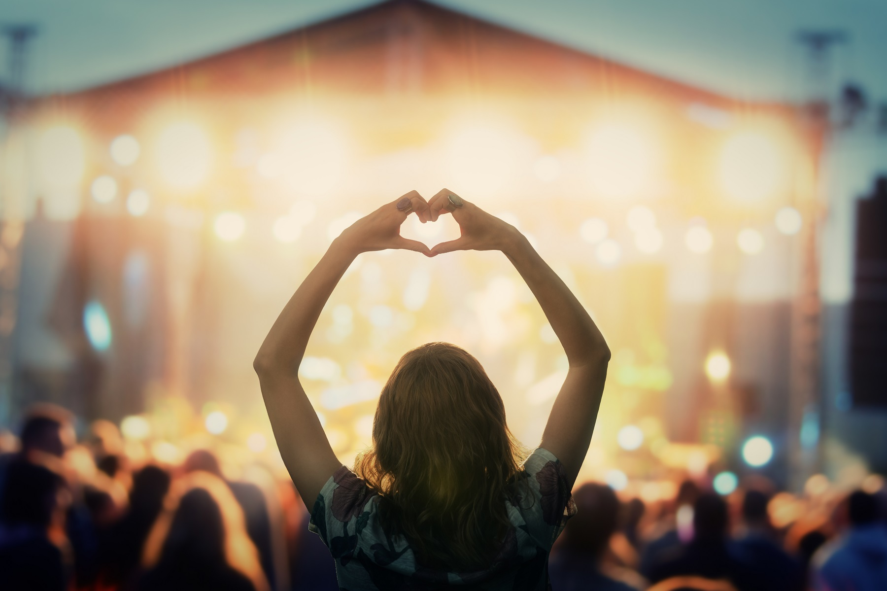 Girl making a heart-shape symbol for her favorite band.