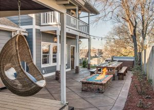 exterior of vacation rental with fireplace and hanging chair on patio