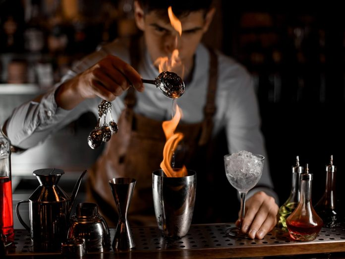 bartender making cocktail with fire