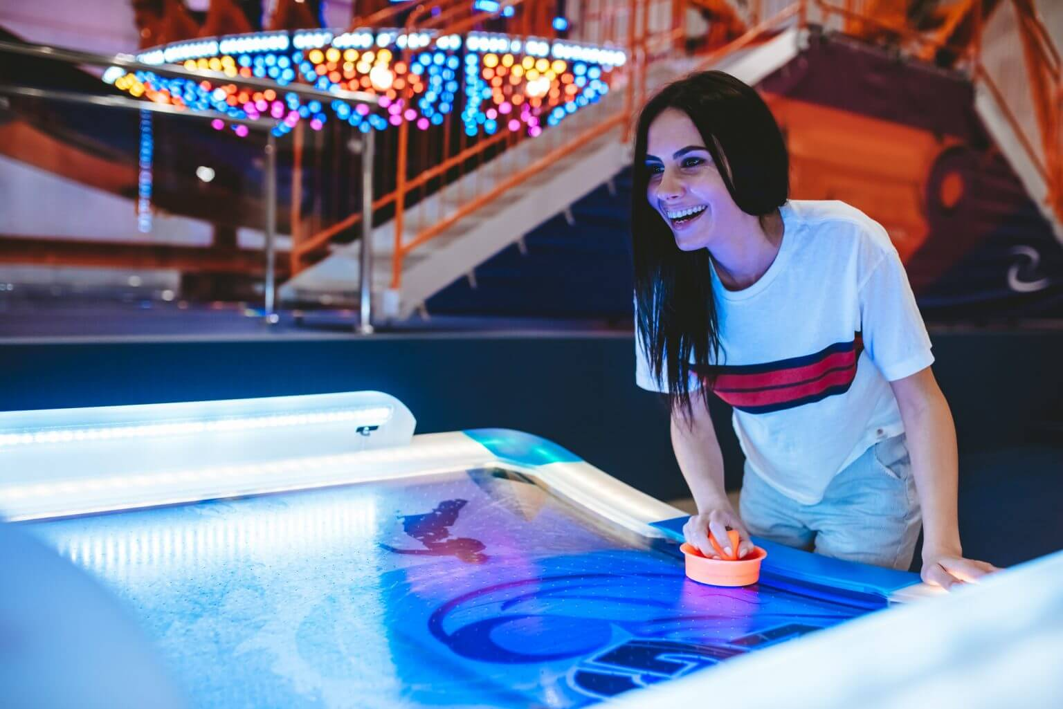 girl playing air hockey in arcade